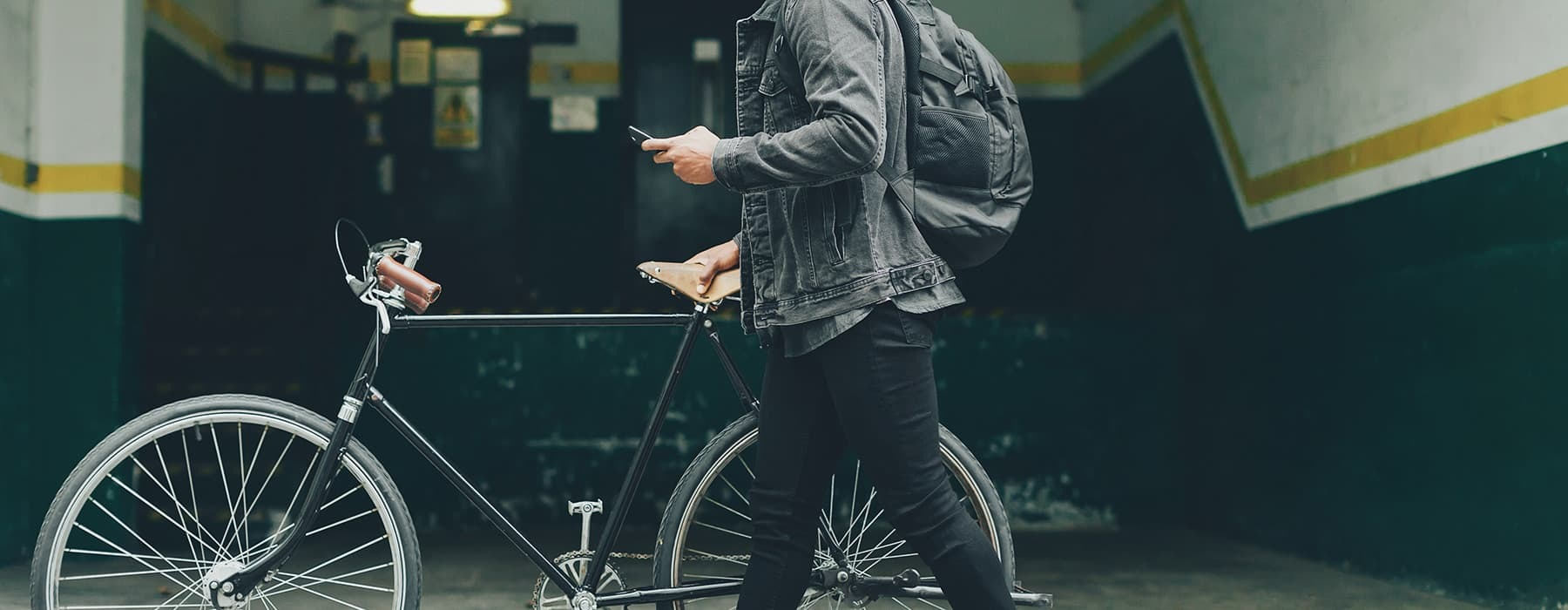 lifestyle image of a person walking with their bicycle