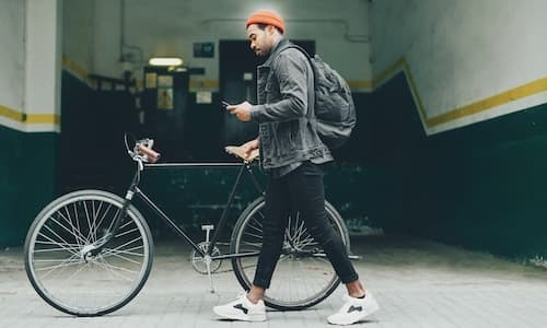 lifestyle image of a man walking with his bicycle
