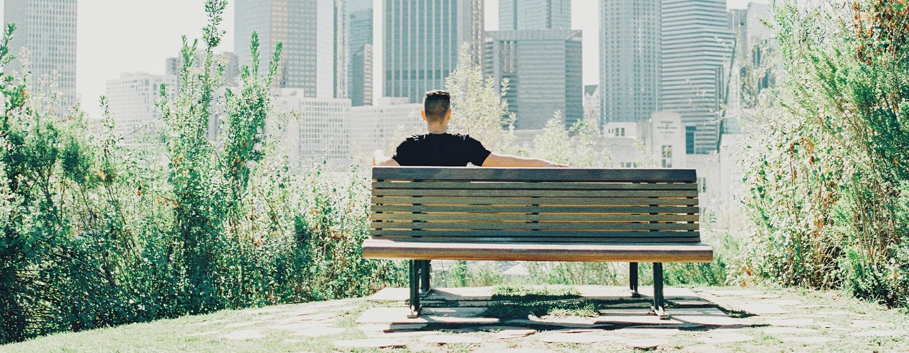 lifestyle image of a person sitting on a bench with city views