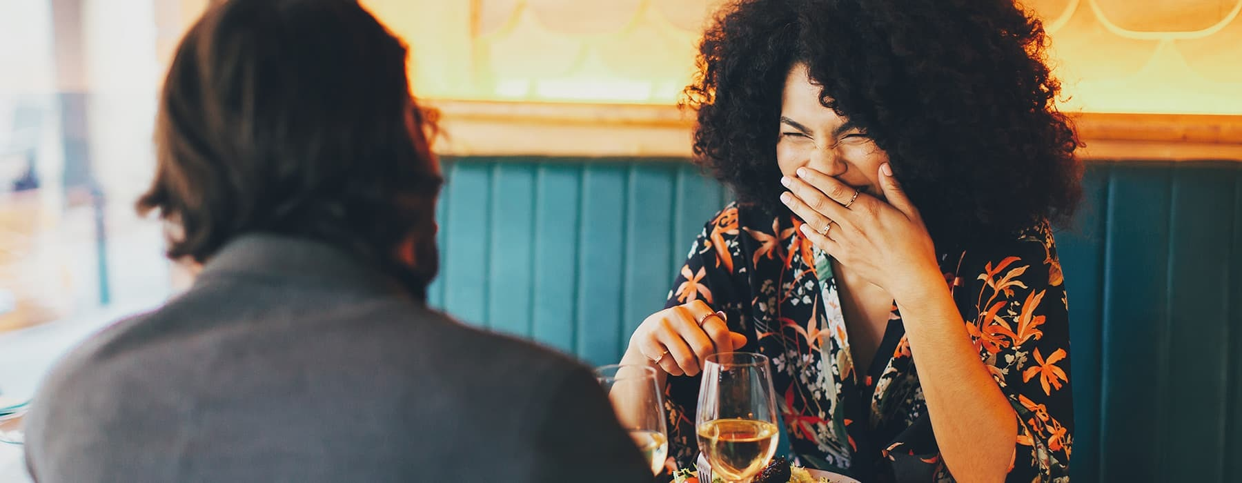 lifestyle image of a woman laughing in a restaraunt