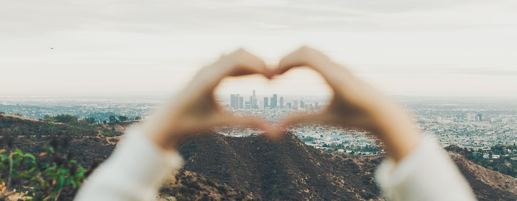 lifestyle image of hands making a heart shape with the distant city in the background